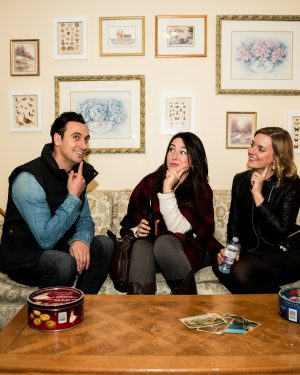 Three people sit on a sofa inside an Escape City escape room, pondering how to get out.